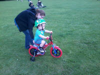 Alfie riding his bike at Kingston Fields, with a little help from Mummy!