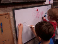 Mason and Alfie making use of the whiteboard at The Norman Tower.