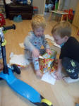 Joshua opening his presents, with help from Alfie.