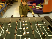 Mason playing table football at Great Ormond Street Hospital whilst waiting for his x-ray.