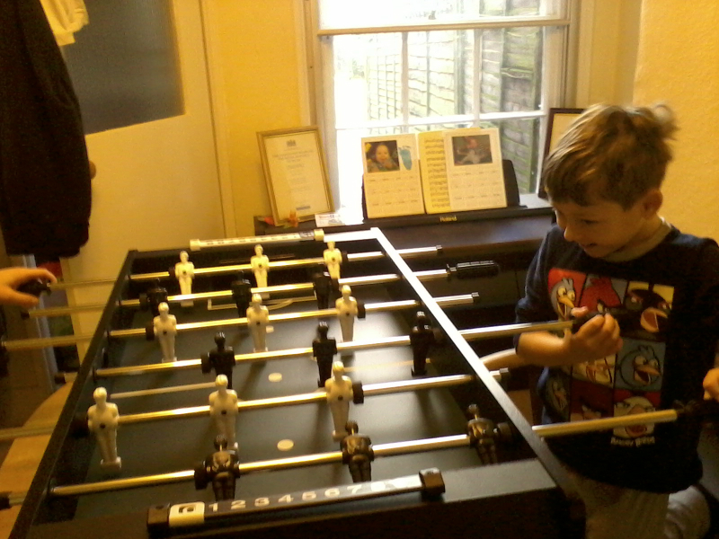 Mason playing on his new table-football at ours.