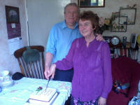 Mum and Dad cutting their cake.