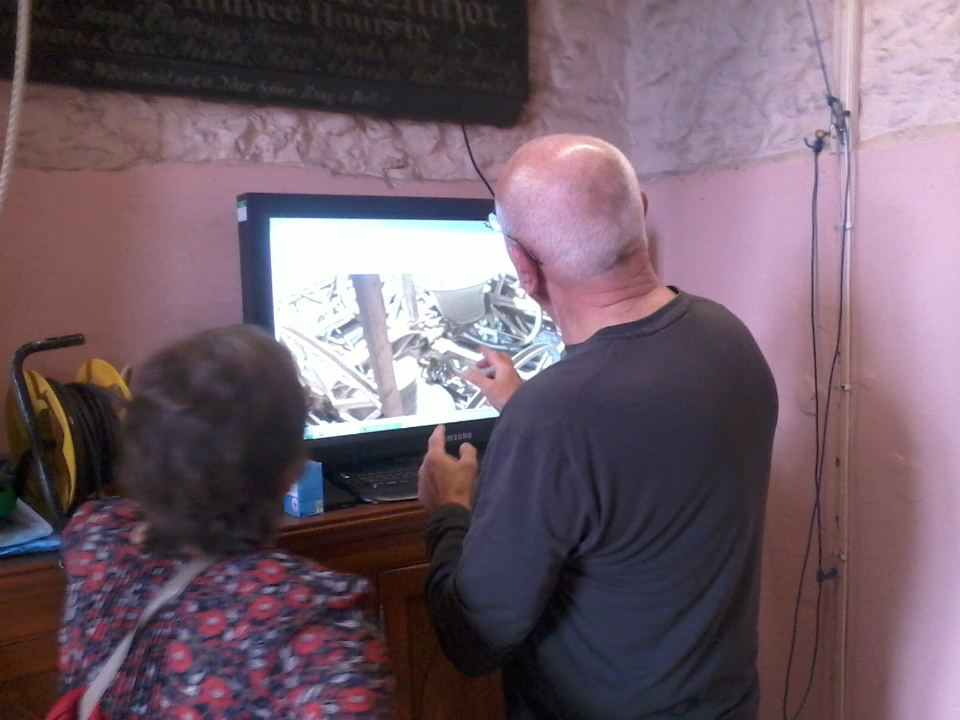 Mike Cowling using the live feed to the bells to explain ringing to a visitor on the tower open day.